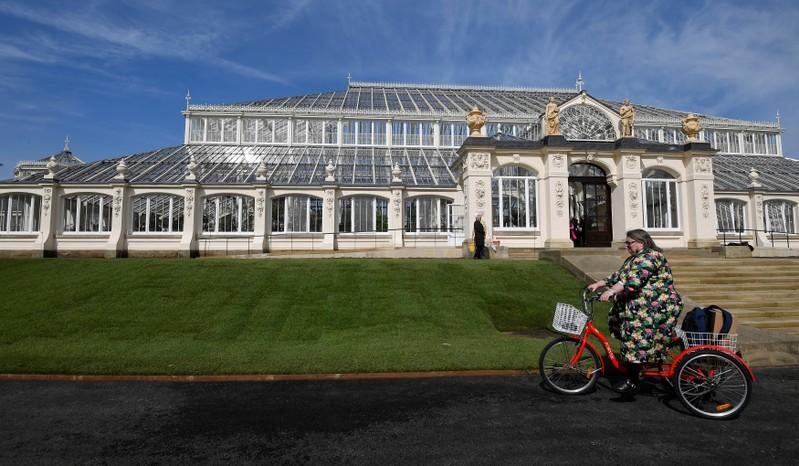 A visitor cycles past the newly restored Victorian Temperate House which has been re-opened to the public following a five year restoration programme in Kew Gardens, London, Britain