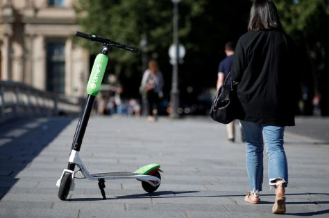 FILE PHOTO: A woman walks past a dock-free electric scooter Lime-S by California-based bicycle sharing service Lime displayed on their launch day in Paris