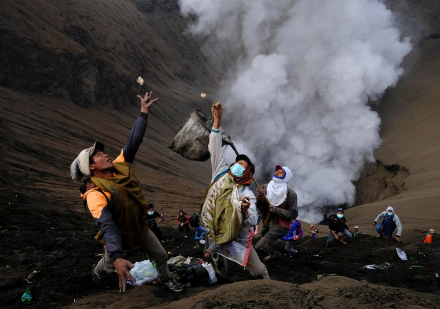 Villagers standing on the slopes near the crater of Mount Bromo try to catch money thrown in by worshippers as smoke and ash rise from the volcano, during Kasada ceremony in Probolinggo
